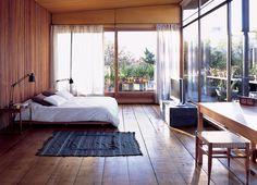wooden minimal bedroom surrounded by a balcony full of plants - alejandro sticotti