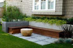Holz-Sitzbank, Hochbeete aus Beton und Ziergräser als Deko