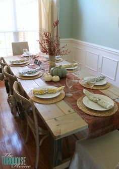 I wrapped an old glass vase in burlap and tied it with a fabric scrap, then filled it with faux berries, twigs and leaves to create my centerpiece. I love a good tall centerpiece on a long table. So cheap and easy!! | Happy Fall-i-Days Home Tour | TheTurquoiseHome.com