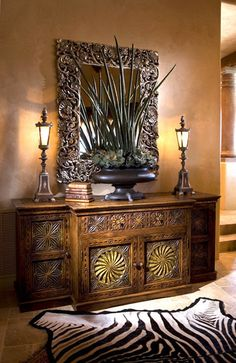 Ornate mirror w/ large floral flanked by two lamps & stack of small books highlight the intricately carved entry table