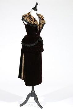 * Balenciaga couture evening ensemble with 'matador' passementerie, circa 1948, un-labelled, of gold backed aubergine silk velvet, bodice with spectacular shaped collar adorned with three dimensional gold braided florets and fronds further embellished with gold sequins and coils of purl wire, hem and collar edged in black 'Spanish' fringing.