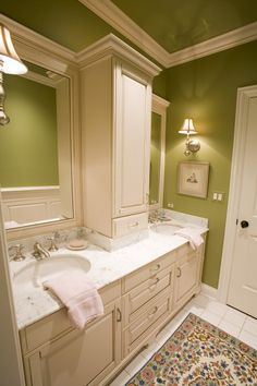 "Countertop middle storage cabinet between vanities and framed mirrors. This is great for small baths with limited storage, but here looks a little ""outstanding"" ... consider using mirror along sides and even on front to create a more open feel to this small area.   Mercury mirror is all the crave now and would make a lovely statement.  Beveled mirror would work well too!"