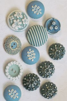 Vintage blue and white buffed celluloid and plastic buttons. -- I especially like the button up to the far left with the flowers.