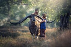 Mother with son riding a buffalo in the field by Sasin Tipchai - Photo 195463571 / 500px