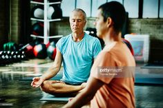 Two mature men in lotus pose during class in studio
