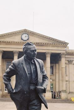 The classic Huddersfield train station, Yorkshire UK with statue of former Prime Minister Harold Wilson who was born in Huddersfield