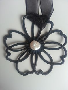 Rubber tattoo with a flower shape. Original and light becomes a must for this summer. It has a Pearl in the middle and the back is layered with leather.