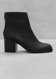 Featuring a chunky heel and an exposed zipper in the back, these matte black leather boots completes a bold autumn look.
