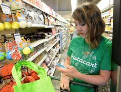 Kaitlin Myers a shopper for Instacart studies her smart phone as she shops for a customer at Whole F... - Cyrus McCrimmon/Denver Post/Getty Images