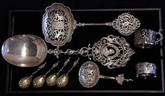 (Dutch .833 silver consisting of Neo-Classical style serving spoon, server with a shaped bowl decorated with a pierced coat of arms, and a bon bon scoop having a pierced bowl decorated with a man smoking a pipe in the foreground and a windmill landscape background; together with an English pierced putti and acanthus scroll demitasse cup by William Comyns, 1899; Barbour Silver Company silver plate open salt; and four silver plate shell spoons