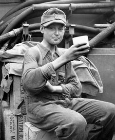Captured German boy soldier enjoys a cup of coffee aboard a U.S. Coast Guard LCI, Normandy coast, 1944