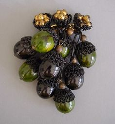 HASKELL bakelite acorn pin of marbled dark green and black acorns with black enameled filigree tops and gold tone metal beads top bar, all suspended from a pierced metal back, 4-1/4. A Frank Hess design for Miriam Haskell, it is unsigned as was typical of this era circa 1940.