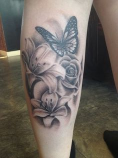 Butterfly tattoos on arm, realistic butterfly tattoo, flower thigh tattoos, lily flower tattoos Realistic Butterfly Tattoo, Butterfly With Flowers Tattoo, Lily Flower Tattoos, Butterfly Sleeve Tattoo, Feminine Tattoos, Girly Tattoos, Pretty Tattoos, Beautiful Tattoos, Thigh Garter Tattoo