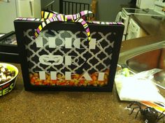 This is a 8x10 shadow box. It can be hung on the wall. Trick or Treat is white vinyl. Box is filled with candy corn (included), decorative