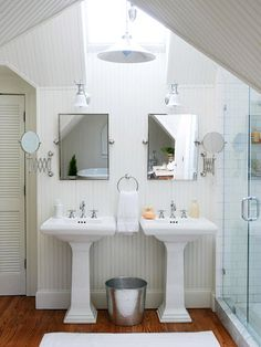 A skylight sheds light on the main task area of the bathroom while taking advantage of the room's peak. With multiple rooflines intersecting, the homeowners opted for simple designs and a neutral color scheme to keep the space serene. Matching pedestal sinks equip this small bath for two users. A glass shower door allows light from the skylight and vanity fixtures to penetrate the shower.