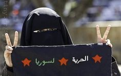 "A veiled Palestinian student flashes V-victory signs while holding a black flag reading in Arabic ""Freedom, Syria"" during demonstration agai..."