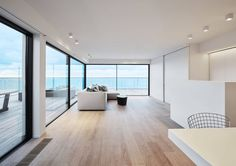 Knokke, a minimalist home in Belgium by design studio minus. Wrap-around balcyon with an ocean view lies just beyond the sparsely furnished living room.