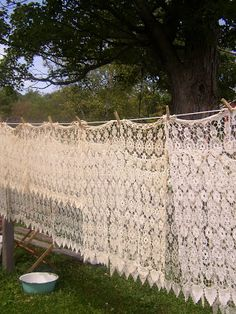 so pretty...a backdrop of lace tablecloths hanging from a line...add some greenery to the top of the line, flowers, ribbons...oh the possibilities of this simple photo of tablecloths drying on a clothes line!