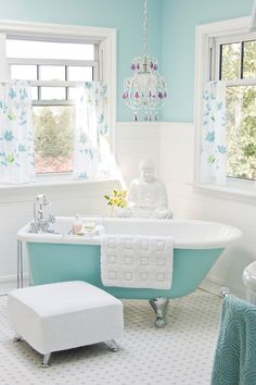 This bright powder-blue and white bathroom brings together eclectic elements like a ceramic buddha, modern ottoman and fiberglass clawfoot tub for a relaxing, spa-like feel. A sparkly chandelier and f