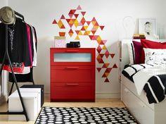 BRIMNES Kommode mit 3 Schubladen in Rot/Frostglas vor einer weißen Wand mit einem geometrischen Muster in Gelb, Rot, Orange und Rosa