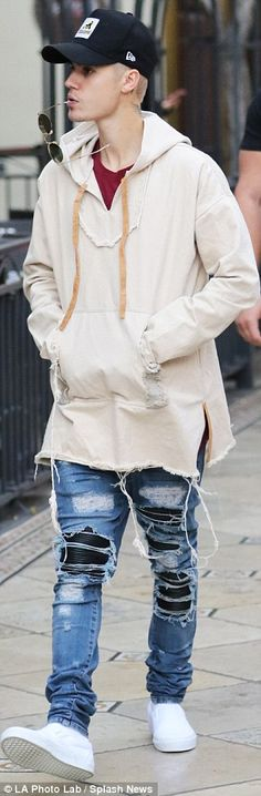 Fashion forward: The singer paired the unique cover up with a maroon t-shirt, white sneakers and ripped medium wash jeans, which included black leather beneath the tears