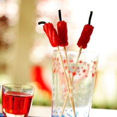 Bring the boom with this faux sparkler drink garnish. They're licorice bit firecrackers with licorice bit fuses.