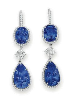 A PAIR OF SAPPHIRE AND DIAMOND EAR PENDANTS Each suspending a pear-shaped sapphire, weighing approximately 9.49 and 8.18 carats, within a circular-cut diamond surround, from a cushion-cut diamond link, weighing approximately 0.60 and 0.57 carat, to a cushion-cut sapphire, weighing approximately 4.24 and 3.79 carats, within a circular-cut diamond surround, the French wire decorated with circular-cut diamonds, mounted in platinum