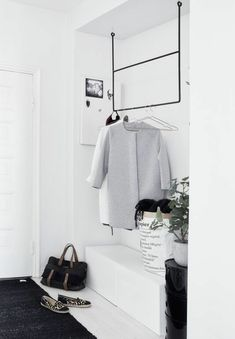 blanc entrée avec tapis noir et vestiaire d'entrée en fer noir, fleurs verts…