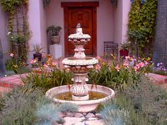 Transforming a new Mediterranean home into a Tuscan villa was the goal. Mission accomplished with an old fountain, lavender, stone edging, vines and a distressed-wood front door.