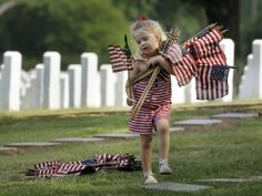 Madeline Grace Wallace, 4, carries flags at the National Cemetery in Little Rock, Ark., Friday, May 25, 2012. The girl and her mother visited the cemetery to place flags on graves for Memorial Day. (AP Photo/Danny Johnston)