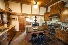 vintage kitchen design with classic and elegant wooden cabinetry plus kitchen island with fancy bar stools: rustic fultonville barn by heritage barns