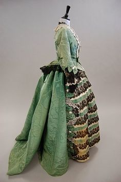 A green watered silk formal gown, circa 1865, the lightly padded bodice trimmed with cream and black lace and bows.