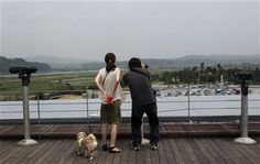 A couple uses binoculars to watch toward North Korea at the Imjingak Pavilion near the border village of Panmunjom which has separated the two Koreas since the Korean War, in Paju, South Korea, Saturday, June 7, 2014. (AP Photo/Ahn Young-joon) ▼7Jun2014AP|North Korea says it is holding an American tourist http://bigstory.ap.org/article/north-korea-says-it-holding-american-tourist-0 #Imjingak_Pavilion #Paju