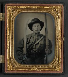 [Unidentified soldier in Confederate uniform with double barrel shotgun, Bowie knife, and two pistols]