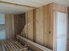 New lighter cedar wall in living room by stairs. Stairs will have a banister. New doors all look like this inside. Washer and dryer are now stacked under stairs.