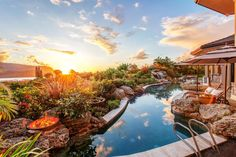 The distant sunset illuminates this tropical paradise's sprawling patio and 50-foot saltwater pool. Flanked by a variety of tropical plants, the pool area includes a picturesque waterfall, firepit and lounge chairs for relaxing.