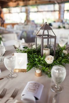 Lantern wedding centerpiece idea - lanterns with greenery wreath and cream roses {Mabyn Ludke Photography}