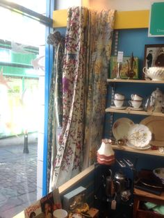 Beautiful floral curtains hanging in the Frome charity shop window #charityshop #frome