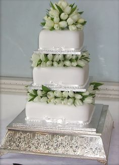 White wedding cake with tulip topper
