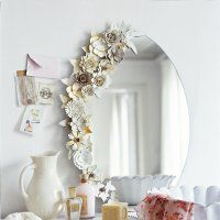 A mirror lined with cardboard flowers ...I think you could also use plaster dipped fabric flowers for a similar effect
