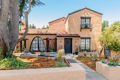 Painting the house multiple colors creates an intriguing lighting effect while emphasizing the home's original Spanish style. Additional seating framing the large window and chevron tile accents throughout the front walkway create beautiful landscape scenery.