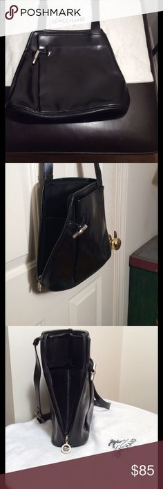 "LONGCHAMP PARIS. Black Smooth Shine Leather Bag. Unique Design zips from lower right up and across left top. Opens wide forward with 5.5""gusset. 2 Interior pockets. Exterior pouch pocket w silver toggle close. Wear over shoulder or ""high cross body"" due to Strap was cut short.  ( see pic 7) Some scuffing and peeling around bottom(pic 8) Some surface blemishes. No rips or tears inside. Measures 11"" high. 10"" across top. 12"" across bottom. Opens 8"" wide. Awesome Style. Longchamp Bags Shoulder…"