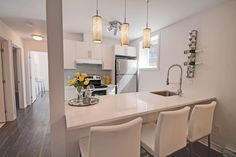 Kitchen staged - model condo - basement unit with alot of natural light - colours are yellows and white and gray.  Le Desaulniers condos in Montreal