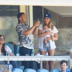 LOS ANGELES, CA - JULY 03: (L-R) John Legend, Luna Simone Stephens and Chrissy Teigen attend a baseball game between the Colorado Rockies and the Los Angeles Dodgers at Dodger Stadium on July 3, 2016 in Los Angeles, California. (Photo by Noel Vasquez/GC I