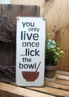"""This wood sign is made from pine, and measures Approx 5.5""""W x 13""""L. It reads """"You Only Live Once Lick The Bowl"""". The front is painted craft white then distressed, the back is stained. We've used a pie"""