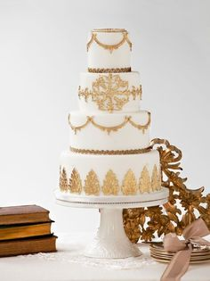 White wedding cake with beautiful gold lace and leaf details