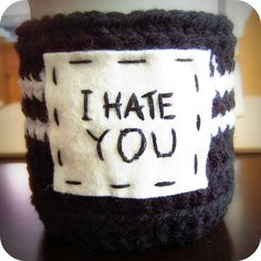 Hand embroidered 'I Hate You' in black cotton thread on real wool felt patch, sewn on handmade crochet black and white striped acrylic coffee tea mug cozy.Ugh.  I hate you.  Well, not you.  You're in my shop and you're reading this.  Presumably then you have a good sense of humor and like cool stuff.  So I like you.  Probably.But, if you're the type of person who oh, I don't know, reaches across me to grab an item on the rack while I'm shopping, then I hate you. If you are t...