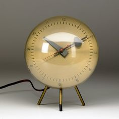 George Nelson; Brass, Glass and Enameled Metal Desk Clock for Herman Miller, c1950.