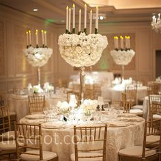 White roses and carnations, candles, and Chivari chairs.