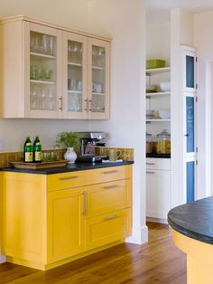 Bold yellow paint graces the lower cabinets and an island in a contemporary style kitchen. Stained Concrete Countertops, White Countertops, Kitchen Pantry Cabinets, Kitchen Dining, Pantry Cupboard, White Tile Backsplash, Yellow Cabinets, All White Kitchen, Kitchen Colors